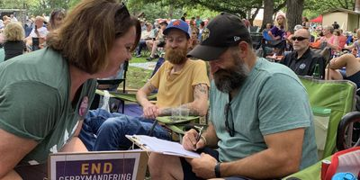 Amy Scott-Stoltz collects petition signatures at the Sioux River Folk Festival on Aug. 7.